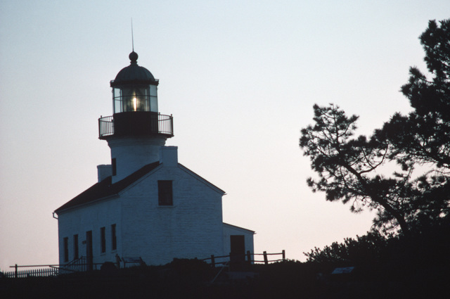 The beacon of the Point Loma lighthouse welcomes ships entering San Diego Harbor at night