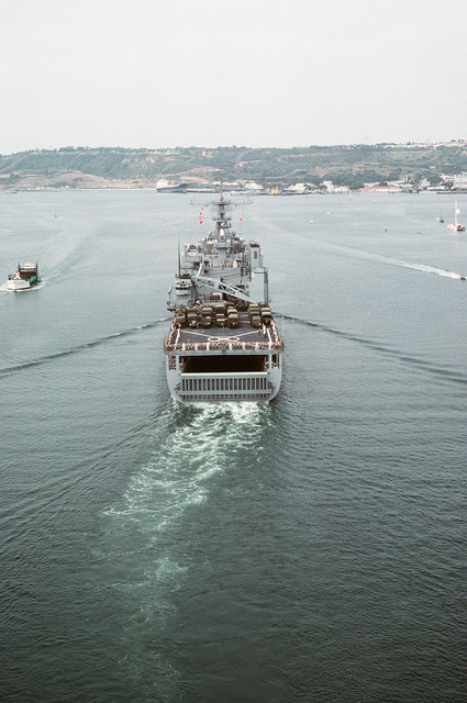 A stern view of the dock landing ship USS FORT MCHENRY (LSD 43) underway with crew members manning the rails