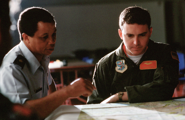 "Major (MAJ) Curtis Garder, left, has a pointer for First Lieutenant (1LT) Robert Nordberg II, copilot, 23rd Bombardment Squadron, 5th Bombardment Wing, who is studying a mission route for his crew during the 15th Air Force's""Shootout""conventional bombing"