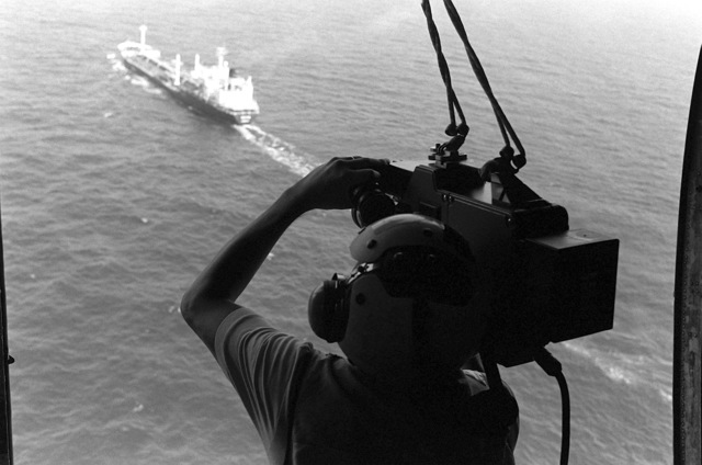 Civilian television cameraman Steve Cocklin videotapes a tanker participating in an Earnest Will convoy mission of tankers heading toward the straits of Hormuz escorted by U.S. Naval ships