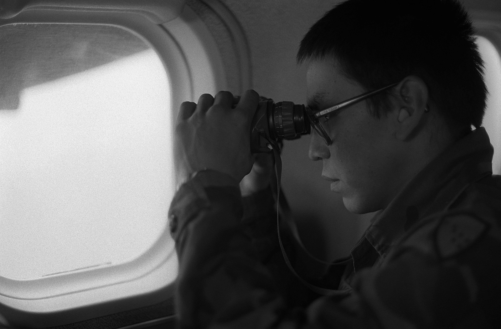 A U.S. military rescue team member uses binoculars to search for seven walrus hunters missing since June 2nd. Searchers received permission to fly three Alaska Army National Guard UV-18 Twin Otter aircraft in restricted airspace after the hunters, from St