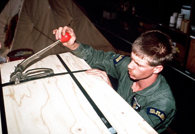 Ian Crafers, a driver with the Royal New Zealand Corps of Transport, seals a supply crate which will be airdropped in Antarctica during MID-WINTER AIRDROP 88.  C-141B Starlifter aircraft of the 63rd Military Airlift Wing will transport supplies to both MC