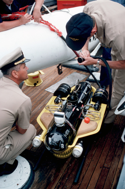 A CHIEF PETTY Officer examines a cable connector for the Super Sea Rover mine locator vehicle as it sits on the deck of the ocean minesweeper USS CONSTANT (MSO 427)