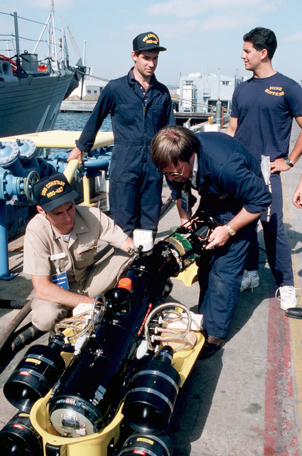 A CHIEF PETTY Officer helps a civilian technician replace an internal component of the Super Sea Rover mine locator vehicle