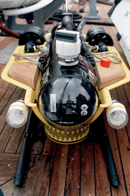 A close-up front view of the Super Sea Rover mine locator vehicle with its top cover removed, showing the vehicle's closed-circuit camera behind the clear plastic nose, as it rests on the deck of the ocean minesweeper USS CONSTANT (MSO 427)