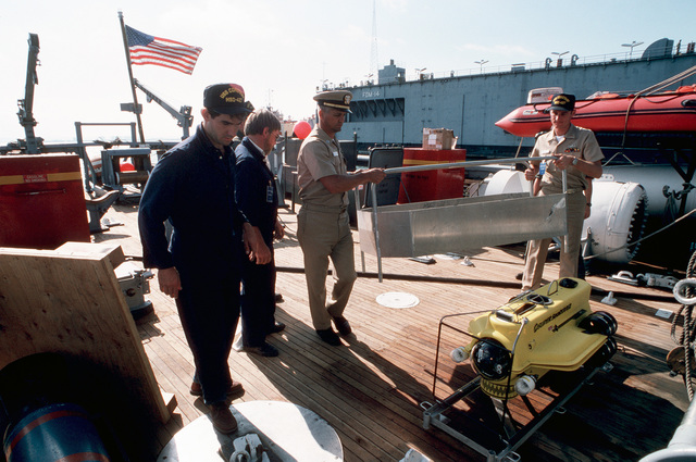 A Lieutenant and a CHIEF PETTY Officer remove a protective housing from around the Super Sea Rover mine locator vehicle on the deck of the ocean minesweeper USS CONSTANT (MSO 427)