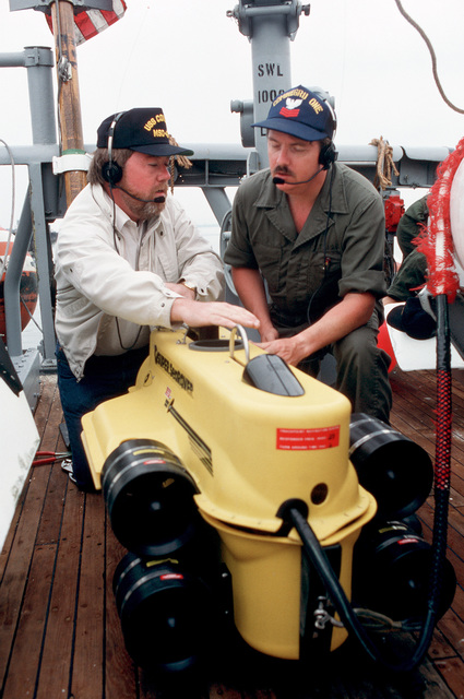A PETTY Officer and a civilian technician kneeling on the deck of the ocean minesweeper USS CONSTANT (MSO 427) examine the Super Sea Rover mine locator vehicle