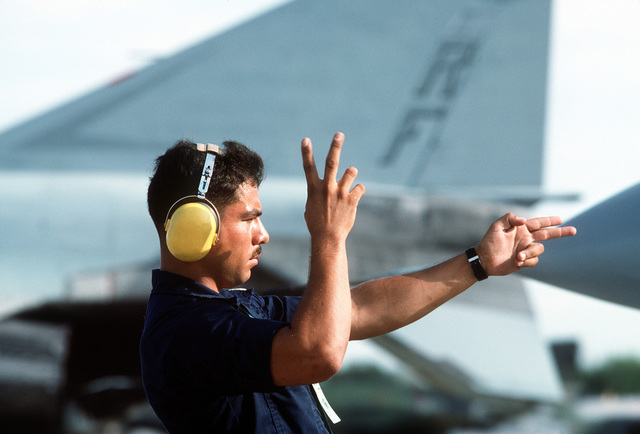 A US Navy crew cheif motions out his team's F-14 Tomcat for a competition mission during Reconnaissance Air Meet 88, a multi-national competition of military aerial reconnaissance teams at Bergstrom Air Force Base. Exact Date Shot Unknown