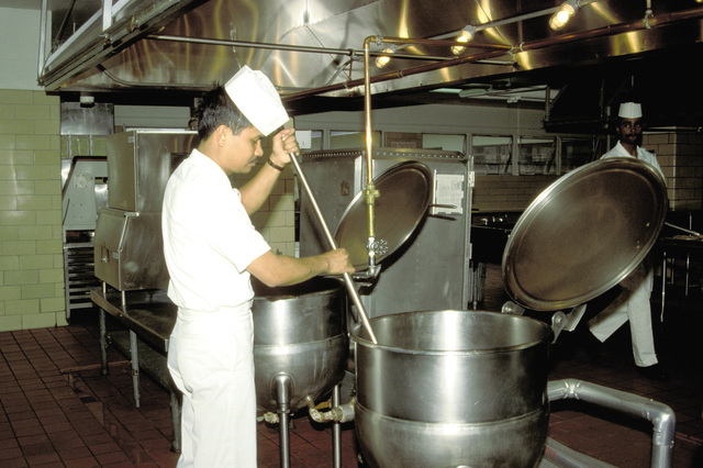 An airman apprentice stirs a soup kettle in the kitchen of the enlisted mess