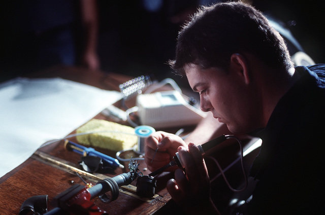 An electrician aboard the ocean minesweeper USS CONSTANT (MSO-427) uses a soldering iron to attach a connector to a section of the control cable for the Super Sea Rover mine locator vehicle