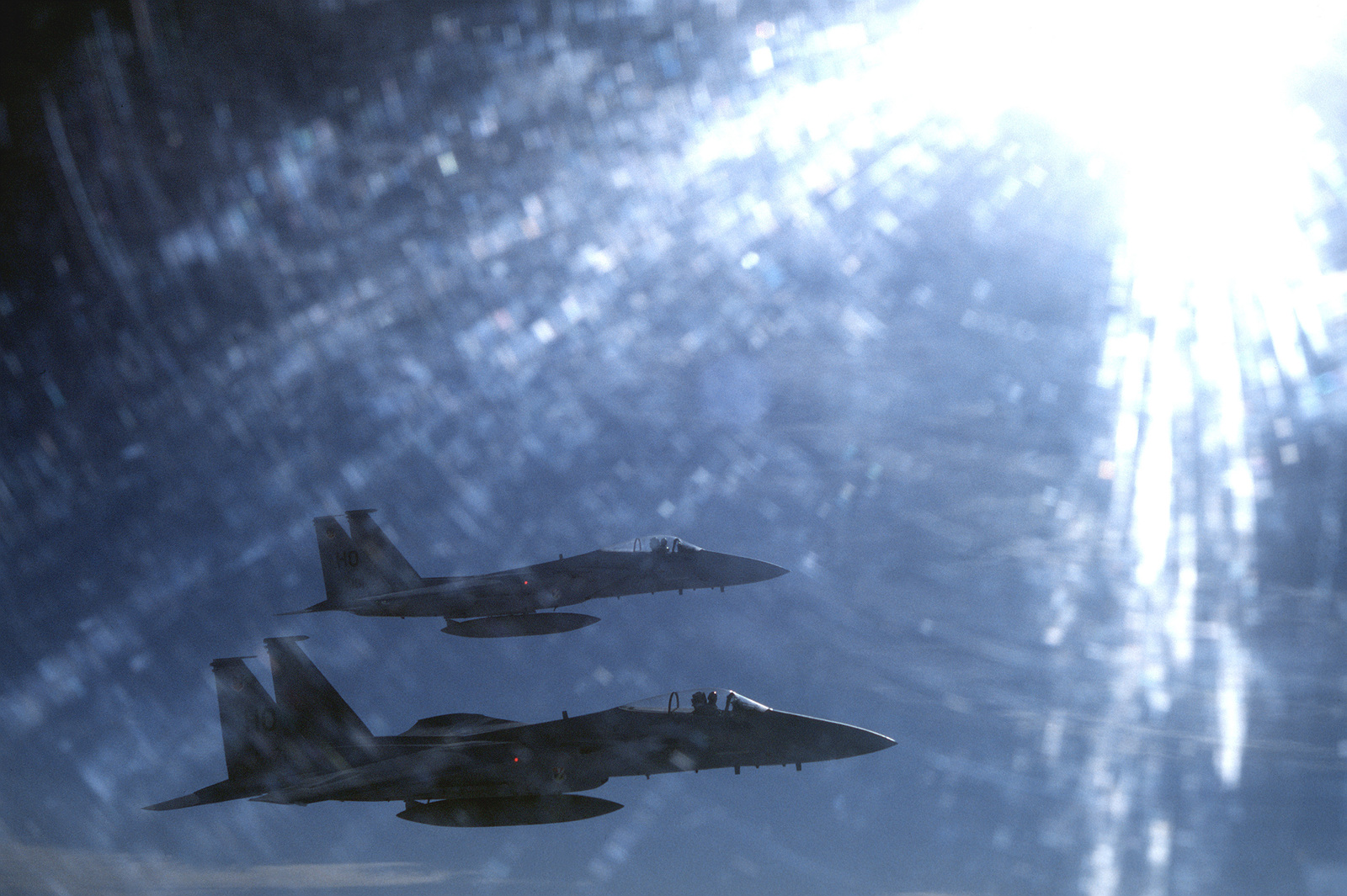 Back lighted air to air view of two F-15 Eagles assigned to the 49th Tactical Fighter Wing, Holloman Air Force Base, New Mexico. Aircraft in foreground is assigned to the 7th Tactical Fighter Squadron. Exact Date Shot Unknown