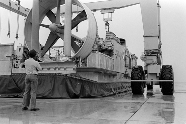 Hull Maintenance Technician 3rd Class (HT3) Dale R. Garren directs a mobile lift into positon to pick up Landing Craft Air-Cushion LCAC-10 craft of Assault Craft Unit 4 (ACU-4) at Naval Amphibious Base, Little Creek, Virginia