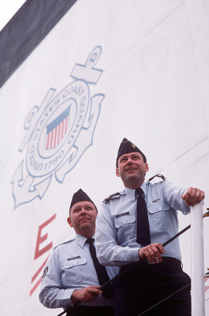 MAJ Joe Hampton and TSGT David Martin, both Air Force officers, stand beneath the Coast Guard emblem at the National Search and Rescue School, a joint Air Force and Coast Guard operation which teaches global search and rescue techniques. Hampton and Martin teach inland search and rescue, a complementary course to the Coast Guard subjects on coastal and oceanic search and implementation
