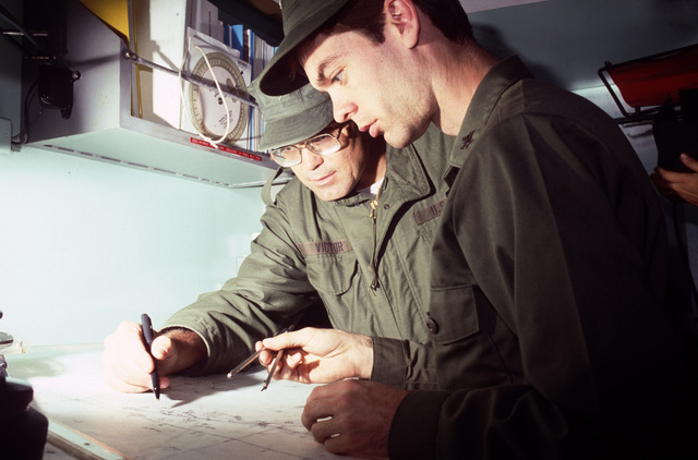 Members of the Mobile Inshore Undersea Warfare (MIUW) Unit 105, USNR, plot grid coordinates on a map inside a mobile trailer during Exercise GALLANT EAGLE '88