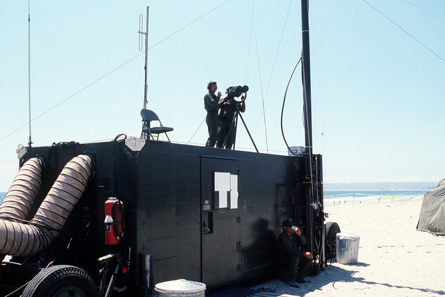 Members of the Mobile Inshore Undersea Warfare (MIUW) Unit 105, USNR, use binoculars to monitor activity from the top of a mobile trailer during Exercise Gallant Eagle '88