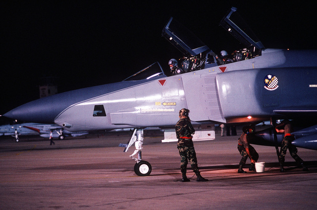 Night view as a U.S. Air Force RF-4C Phantom aircraft and crew on the flight line ramp after a competition mission during Reconnaissance Air Meet 88, a multi-national competition of military aerial reconnaissance teams at Bergstrom Air Force Base. Exact Date Shot Unknown