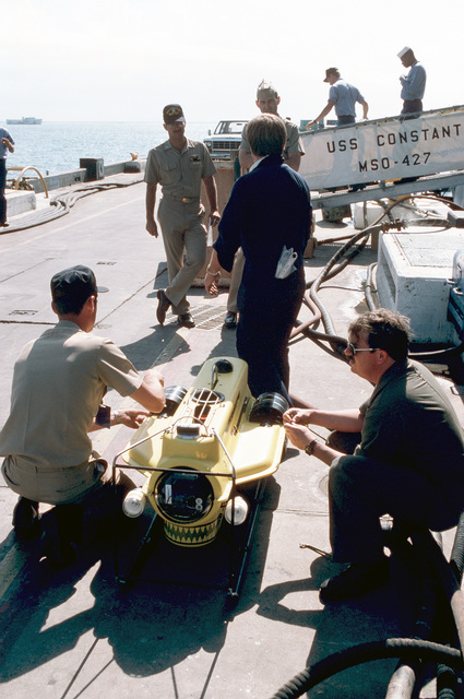 On the pier alongside the ocean minesweeper USS CONSTANT (MSO 427), a CHIEF PETTY Officer and a Sailor attach some of the external components of the Super Sea Rover mine locator vehicle