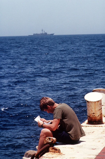 Operations SPECIALIST Derek Galatro reads a letter from home as the guided missile frigate USS HALYBURTON (FFG-40) patrols on the horizon. Galatro is on assignment in the Persian Gulf during Earnest Will, a convoy mission in which reflagged Kuwaiti tankers are escorted through waters of the Gulf by U.S. naval ships