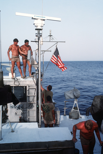 The national ensign is hoisted aboard a PB Mark III patrol boat, part of Special Boat Unit 20, in preparation for an all-night patrol during Earnest Will, a convoy mission in which reflagged Kuwaiti tankers are escorted through waters of the Gulf by U.S. naval ships