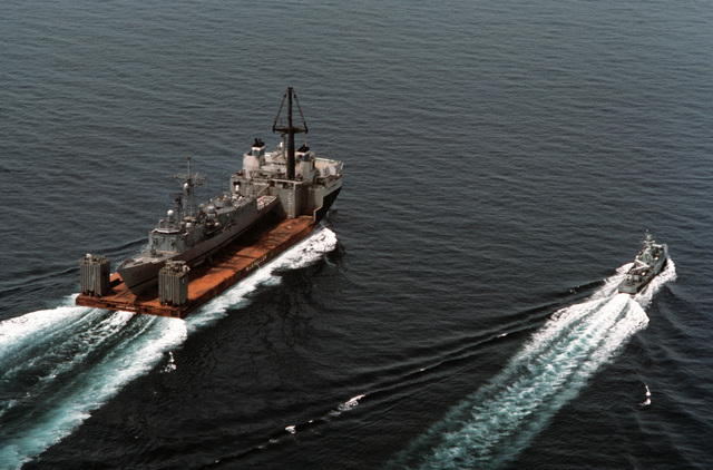 A starboard quarter view of the Dutch heavy-lift ship MIGHTY SERVANT II with the guided missile frigate USS SAMUEL B. ROBERTS (FFG 58) on deck in the Straits of Hormuz.  An Omani Province class fast attack craft is travelling alongside the MIGHTY SERVANT as it transports the frigate, which was damaged when it struck an Iranian mine on April 14, 1988, to its home port in Newport, Rhode Island (RI)