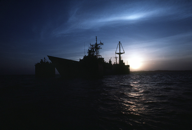 The guided missile frigate USS SAMUEL B. ROBERTS (FFG-58) is silhouetted by the setting sun as it is transported on the deck of the Dutch heavy-lift ship MIGHT SERVANT II. The MIGHTY SERVANT is transporting the frigate, which was damaged when it struck an Iranian mine on April 14, 1988, to its home port in Newport, R.I