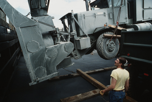 A longshoreman watches as an Oshkosh dump truck, equipped with a snow plow, is loaded aboard a barge by crane during Operation XOOL BARGE '88, a resupply mission by which goods and equipment are delivered to remote Air Force sites in Alaska