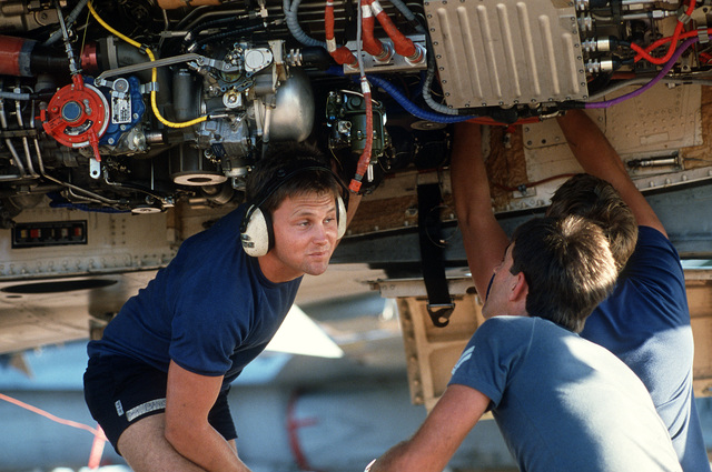 Greg Walker, Eric Holgate, and Dave Banks of Royal Australian Air Force Squadron 3 perform maintenance work under their F-18A Hornet aircraft during Pitch Black '88, a joint Australia - U.S. exercise emphasizing night flying