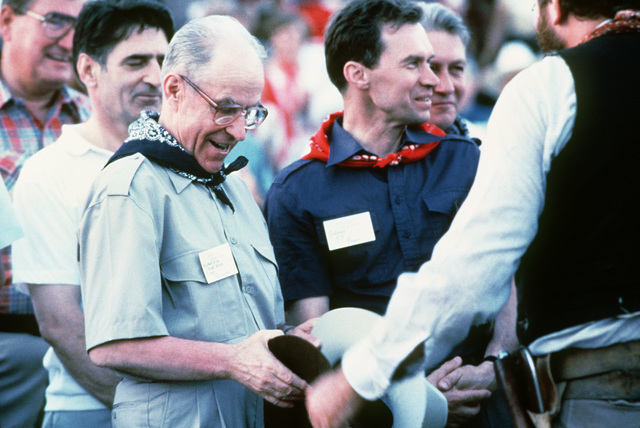 Marshal Sergei F. Akhromeyev, First Deputy Minister of Defense and CHIEF of the General STAFF of the Soviet Union, is presented with a souvenir cowboy hat while attending a cattle branding exhibit.  The marshal is being introduced to such local forms of e