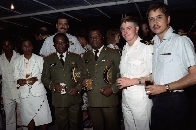Lieutenant (LT) Peralta, right, Lieutenant Junior Grade (LTJG) Eldridge, and CHIEF Warrant Officer (CWO) Kabick, background, attend a gathering hosted by local residents.  The tank landing ship USS SUMTER (LST 1181) is visiting the city during a six-month