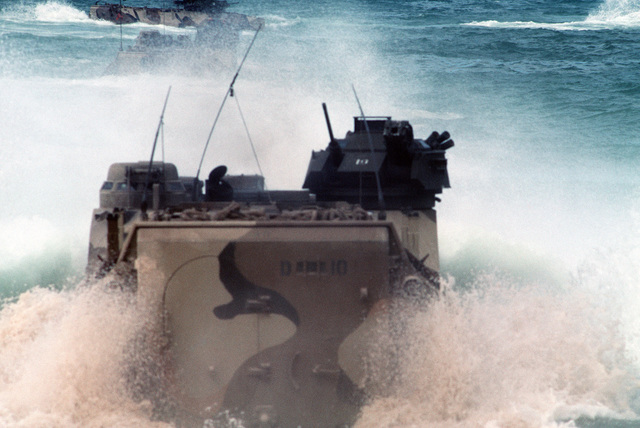 An AAVP7 assault amphibian vehicle (AAV) churns up sand and water as it follows two other AAVs off the beach and into the surf to return to their ship at the conclusion of Exercise RIMPAC 88.  The AAVs are from Marine Corps Base, Twentynine Palms, Califor