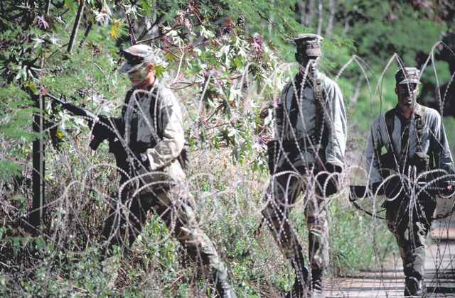 """Three Marines from the 3rd Marine Regiment, 1ST Marine Brigade, wearing their camouflage blouses inside out to distinguish them as """"aggressors,"""" bypass a roll of concertina wire while on patrol during Exercise RimPac '88"""
