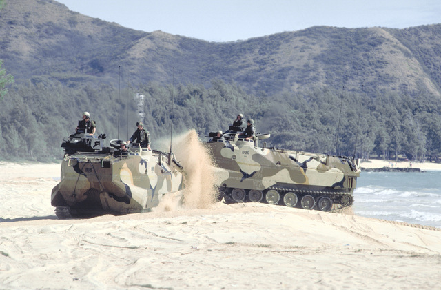 Two AAVP-7 assault amphibian vehicles (AAVs) churn up a sand as they move onto the beach after leaving a Navy ship during Exercise RimPac '88. The AAVs are originally from Marine Corps Base, 29 Palms, California