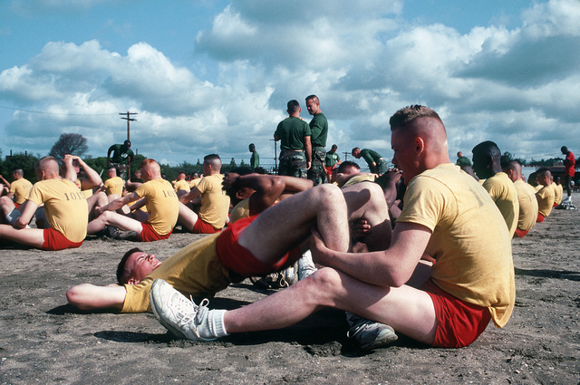 A Marine Corps recruit holds another recruits legs while he performs sit-ups during physical training at the Recruit Training Depot, San Diego
