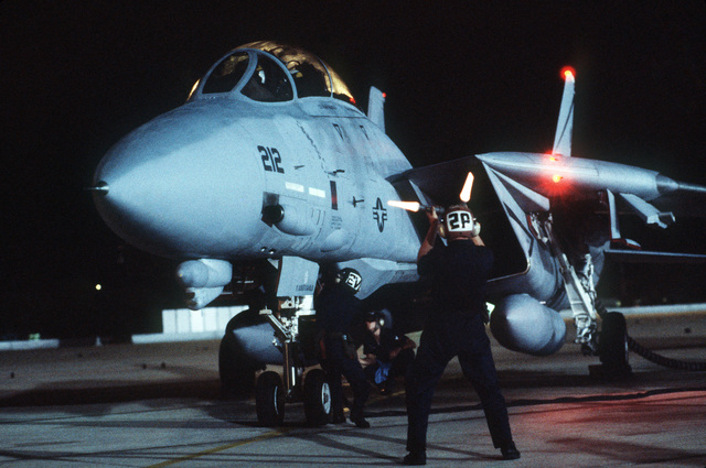"""A ground crewman signals the pilot of an F-14A Tomcat aircraft as other crewmen service the plane on the flight line during Reconnaissance Air Meet""""88.  The international competition is being hosted by the 67th Tactical Reconnaissance Wing at Bergstrom Ai"""