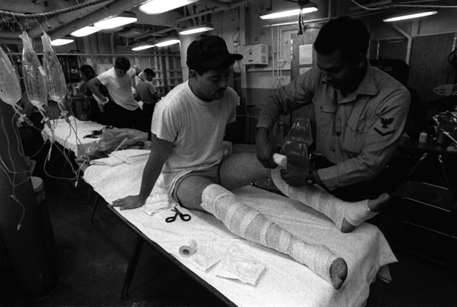 A corpsman wraps the legs of one of the crewmen injured during an engine room fire aboard the aircraft carrier USS CONSTELLATION (CV-64)