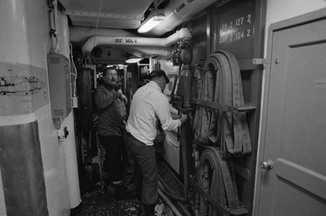 Members of the fire party connect a hose to a fire main while fighting an engine room fire aboard the aircraft carrier USS CONSTELLATION (CV 64)