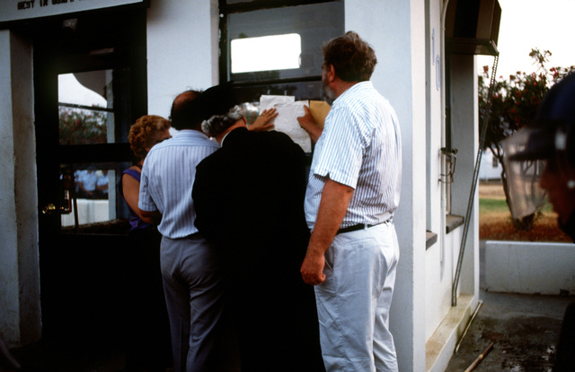 At the main entrance to the base, a priest and other protest leaders post a petition for the removal of American military presence from the country