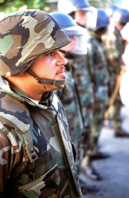 Sergeant (SGT) Garcia of the 7276th Security Police Squadron stands firm in the line established against demonstrators protesting the American military presence in Greece