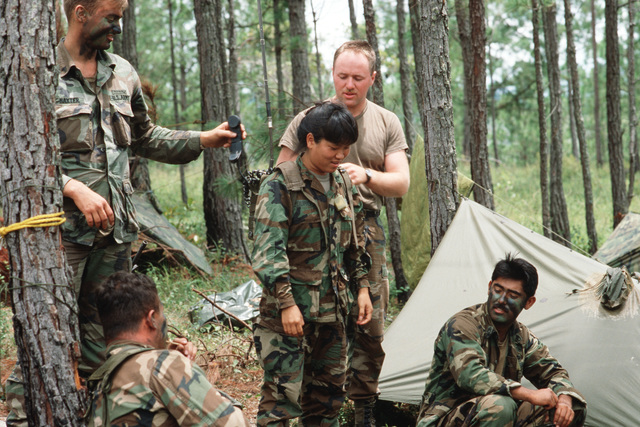Members of the 7th Infantry Division (Light) demonstrate use of the field radio to Private First Class (PFC) Kim S. Young during Exercise CABANAS 88, a Joint Chiefs of STAFF exercise designed to promote and increase effective interaction between participa