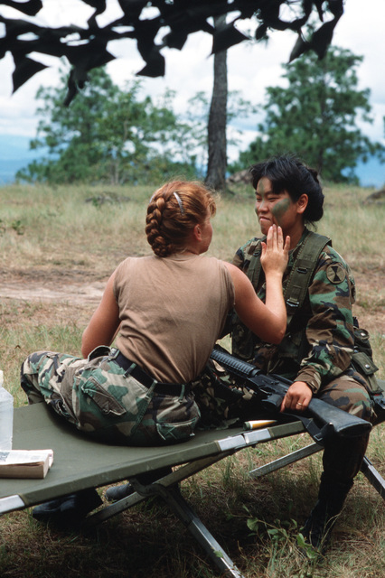 SPECIALIST Fourth Class (SPC) Krissy M. Palacios applies camouflage to Private First Class (PFC) Kim S. Young, both from the 7th Infantry Division (Light), during Exercise CABANAS 88, a Joint Chiefs of STAFF exercise designed to promote and increase effec