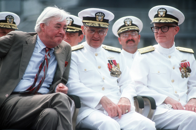 Vice Admiral (VADM) William H. Rowden, commander, Naval Sea Systems Command, speaks with Senator Daniel P. Moynihan, Democrat-New York as Rear Admiral (RADM) (upper half) Grant A. Sharp, assistant deputy chief of naval operations, Surface Warfare, looks on during the commissioning ceremony for the guided missile cruiser USS LAKE CHAMPLAIN (CG 57)