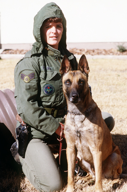 SGT. Michelle Putnam poses for a photograph with her dog Carlos prior to taking part in an explosives training exercise at the Security Police Academy. The school provides fundamental courses in law enforcement and security duties for Air Force personnel as well as advanced training to security police of all ranks and branches of the armed services