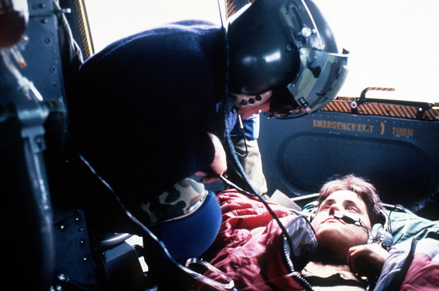 TECH. SGT. Edward D. Lindsey, 304th Aerospace Rescue and Recovery Squadron talks to a woman suffering from hypothermia (loss of body heat) over the intercom of the Squadron's HH-1 Iroquois helicopter that is transporting her to the hospital. The Air Force Reserve squadron is based at Portland International Airport