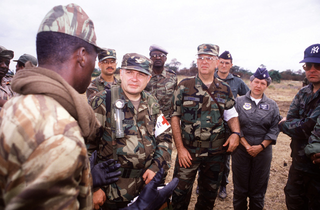 A Gabonese soldier speaks to members of a joint U.S. Army, Navy and Air Force team during Gabon Medflag '88, an exercise providing medical assistance and training to the people of Gabon