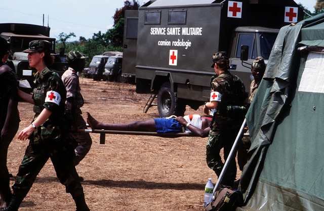 Gabonese military personnel transport a simulated patient on a litter as members of a joint U.S. Army, Navy and Air Force team supervise during Gabon Medflag '88, an exercise providing medical assistance and training to the people of Gabon