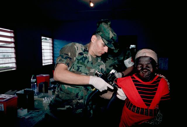A woman winces as she gets a yellow fever immunization from SPECIALIST Fourth Class (SPC) Kelly Williams of the 97th General Hospital.  Villagers are being immunized against mumps, polio, measles, rubella, yellow fever and typhoid during Gabon Medflag 88
