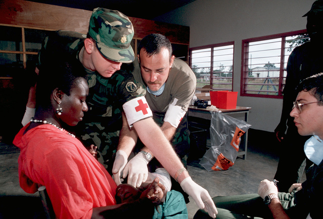 Personnel from the 97th General Hospital and the 142nd Aeromedical Evacuation Squadron work with a Gabonese woman and her child, in a medical clinic set up for Gabon Medflag 88.  Villagers are being immunized against mumps, polio, measles, rubella, yellow