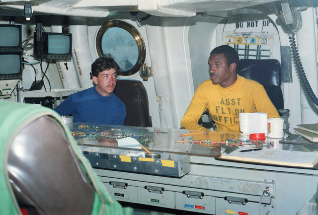 Crewmen plot aircraft spotting positions in the flight deck control center of the aircraft carrier USS FORRESTAL (CV 59) in the North Atlantic Ocean during Exercise WEST WIND 88