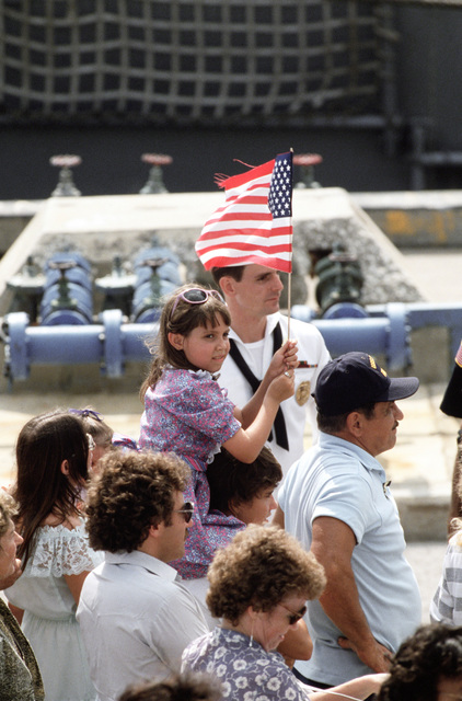 A girl holds an American flag as she and others await the return of the guided missile frigate USS STARK (FFG 31) to its home port.  The STARK has just completed sea trials that followed a stay at the Ingalls Shipbuilding facility in Pascagoula, Mississippi, for repairs to the extensive damage caused by two Iraqi-launched Exocet anti-ship missiles that struck the ship while it was on patrol in the Persian Gulf in May 1987.  Thirty-seven crewmen were killed in the explosion and fires