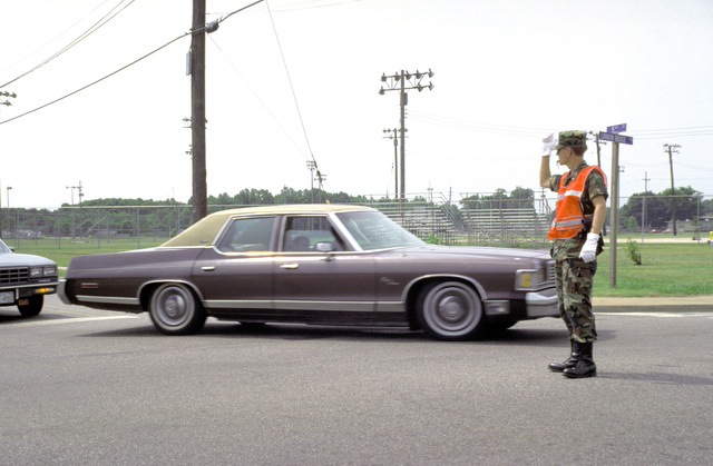 A member of the air station's security department directs lunchtime rush traffic at an intersection